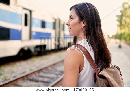 friendly brunette backpacker planning her trip and consulting her mobile phone in a train station at sunset