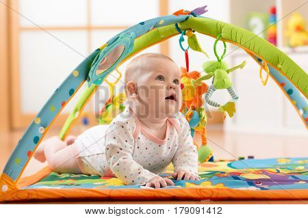 Happy seven months baby girl plays lying on colorful playmat in nursery