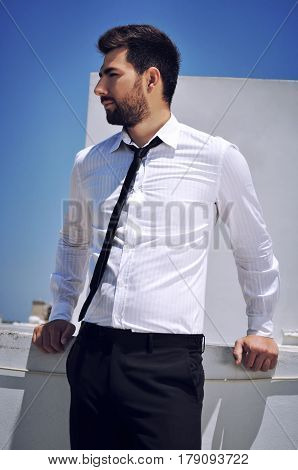 Hispanic looking young man standing outside in sunny weather wearing a black tie and a white shirt.