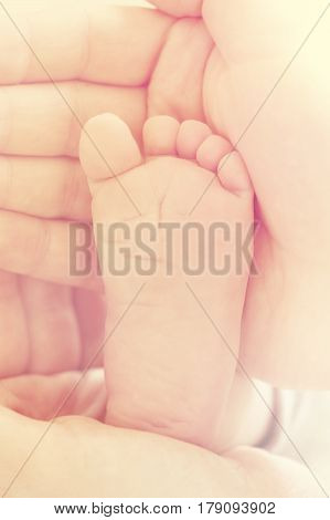 Closeup of mother hands holding cute tiny baby feet showing baby foot. Selective focus. Toned.