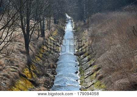 Drainage ditch between fields. Water. Spring scenery.