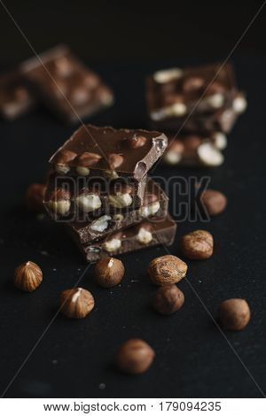 Chocolate Bar Pieces And Nuts On Dark Slate Background With Copy Space. Chocolate Background. Top Vi