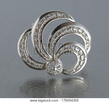 Vintage filigree silver brooch on gray background with mirror reflection
