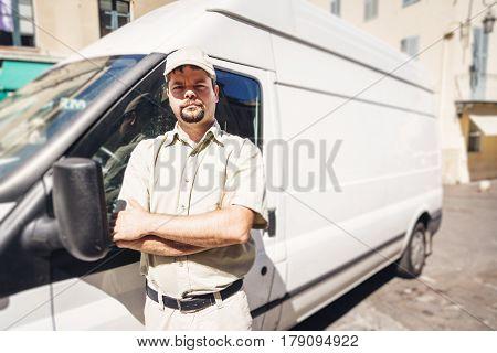 Messenger standing next to his van in urban setting