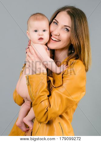 Newborn Baby Smille In Mother's Hands Isolated On Grey Background
