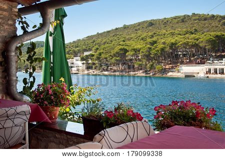 Mediterranean restaurant near the blue sea. Flowerpots with pink flowers standing near the tables and a metal downspout. Hills covered in green verdant forest. Blue cloudless sky. Dugi otok Croatia