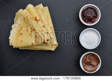 pile of french pancakes on dark background with sugar chocolat and jam on little jar