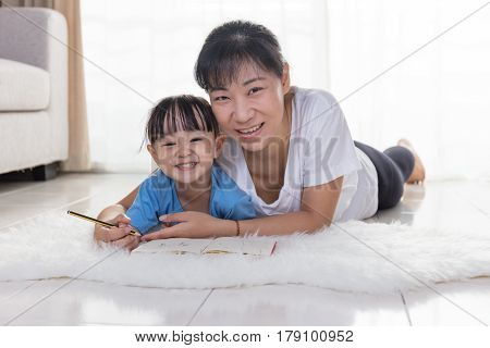 Happy Asian Chinese Mother And Daughter Writing On The Floor
