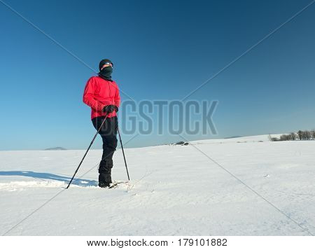 Man cleaning snowshoe. Winter tourist with snowshoes walk in snowy drift. Sunny freeze weather. Hiker in pink sports jacket and black trekking trousers snowshoeing in powder snow.
