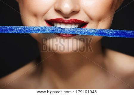 Picture of cheerful girl's lips holding sweeties with teeth. Over grey background