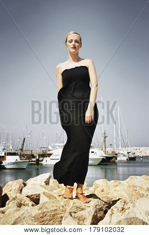 Blonde woman wearing a long strapless maxi dress standing on a rocky seawall on a sunny but windy summer´s day.