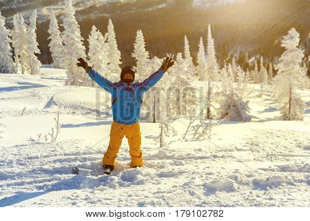 A snowboarder with his hands up on the slope of the ski resort of Sheregesh.