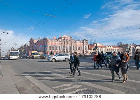 SAINT-PETERSBURG, RUSSIA, MARCH 29, 2017: People cross the Nevsky Avenue near The Anichkov Bridge with The Horse Tamers by Peter Klodt. On the background is Beloselsky-Belozersky Palace