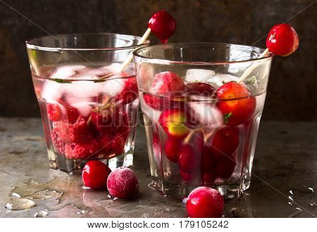 Nonalcoholic drink cocktail of fresh fruit: cherry, raspberry . Concept of a healthy drink. Rusty metal background. Two cans of glasses.