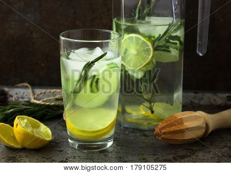 Nonalcoholic drink cocktail of fresh fruits: cucumber, lime, rosemary concept of a healthy drink. Rusty metal background