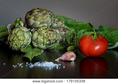 Bunch of artichokes with tomato, garlic clove and coarse salt