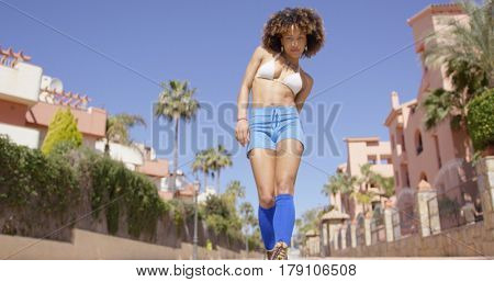 Female wearing blue shorts and knee-high socks looking at camera on city background.