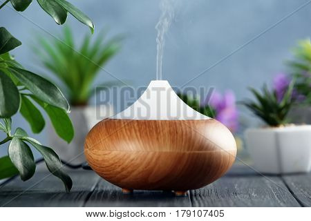 Aroma oil diffuser on wooden table