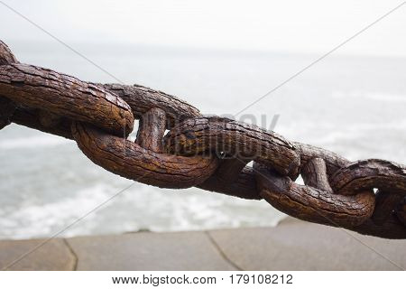 A Rusted, textured and weathered old chain.