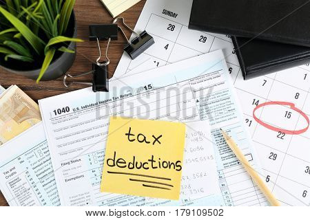Paper sheet with text TAX DEDUCTIONS and individual tax return form on table