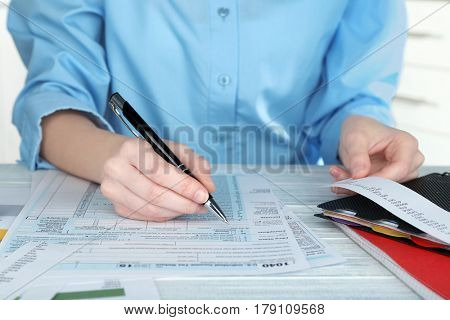 Woman filling form of Individual Income Tax Return, closeup