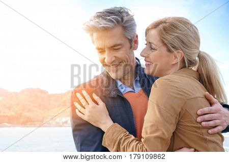 Middle-aged couple embracing each other by the sea, San Sebastian