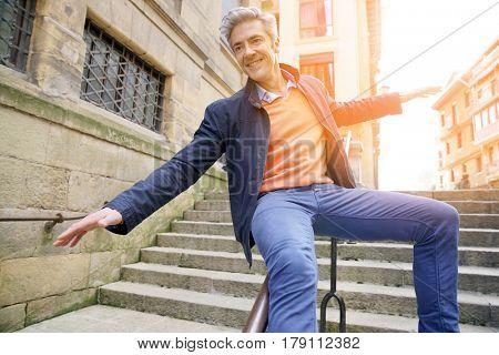 Man having fun sliding down staircase ramp