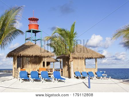 Morning view of wooden shelters and chairs on tourist island Little Stirrup Cay (Bahamas).