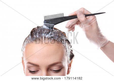 Hairdresser dyeing hair of woman on white background