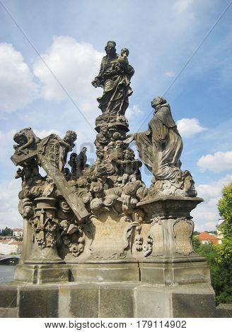 Ancient sculptures on Charles Bridge (Czech: Karluv most) historic famous bridge crosses Vltava river in Prague old town, Czech Republic. Popular travel tourist landmark with architecture classic houses