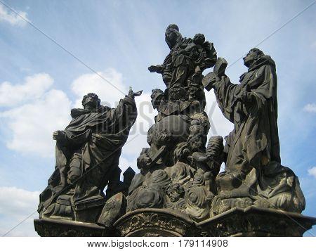 Sculptures on Charles Bridge (Czech: Karluv most) historic famous bridge crosses Vltava river in Prague old town, Czech Republic. Popular travel tourist landmark with architecture classic houses