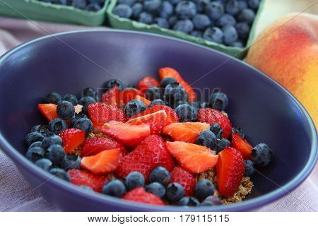 Purple cereal bowl with sliced strawberries and blueberries. Sitting on light purple and white linen napkin. Containers of blueberries and a peach in the background. Selective focus on cereal bowl.