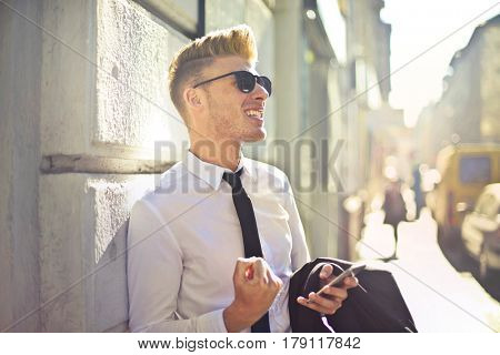 Successful young businessman standing outdoors in a spring day