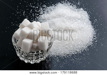 white sugar closeup studio photography. Bowl of white granulated sugar and refined on black surface close-up