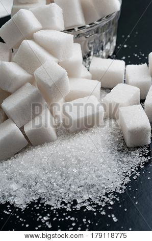 white granulated and refined sugar on black surface close-up