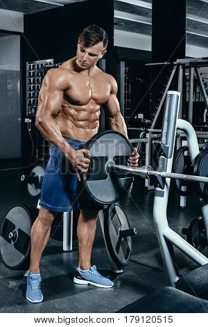Portrait of a handsome man resting near bar in fitness gym and looking aside. Athlete in shorts without T-shirt