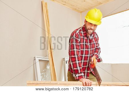 Craftsman holding saw and cutting wood at construction site