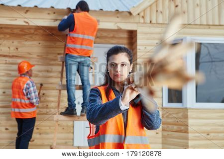 Woman as craftsman building new woodhouse with team