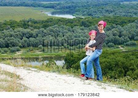 Adult and child standing on a mountaintop near river. Mother with little daughter hiking in mountains on vacation