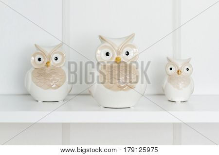 Decorative white oceramic owls on white shelf
