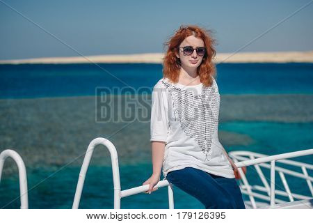 Beautiful ginger woman in sun glasses sits on a white yacht in a sea with clear turquoise water. Relaxation at summer vacation under a sun. Woman looks to the camera.