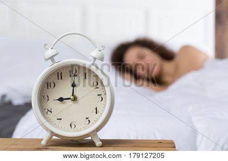 White alarm clock on the background of a sleeping girl. The girl on the bed is blurred. She lies on her right side. 9 o'clock.