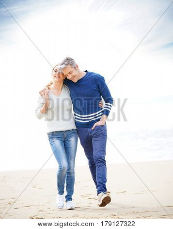 Middle-aged couple walking on the beach, full length