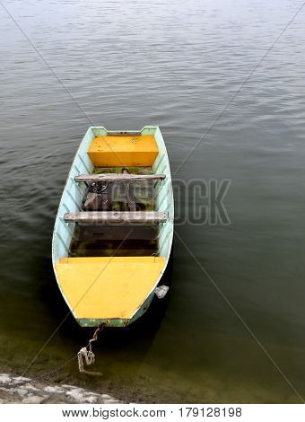 yellow row boat tied to the mound on the dock