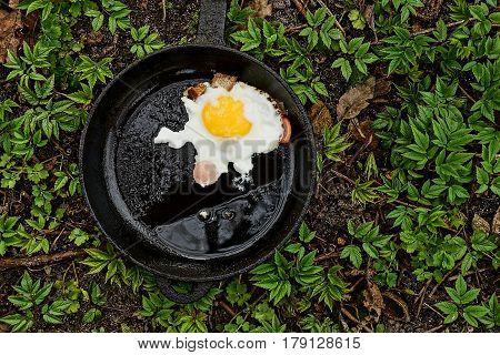 Frying pan with fried egg, sausage pieces and breadcrumbs
