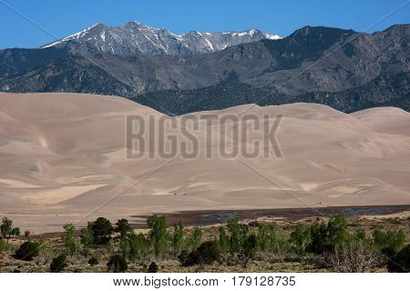Layers of the Great Sand Dunes National Park show high prairie, sand, and the mountains of the Sangre de Cristo range near Alamosa, Colorado in springtime