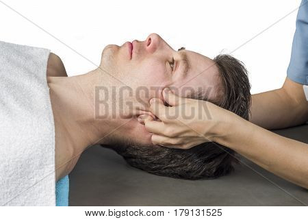 Physiotherapist Doing A Cranial Sacral Therapy To A Man Patient On White Background.
