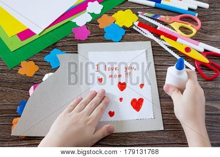 The Child Glues The Details From The Paper To The Postcard. Greeting Card With Flowers On Mother's D