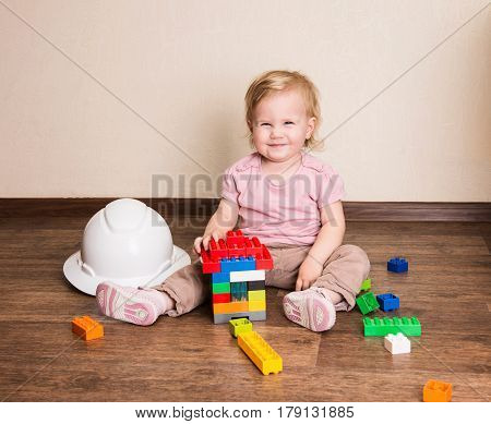Funny baby toddler building a house of plastic constructor blocks. Happy child playing with constructor toys.