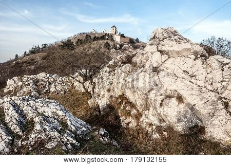 Svaty Kopecek hill with chapel and stations of the cross from rocky Olivetska hora hill in Palava mountains above Mikulov in South Moravia near borders with Austria during nice spring day with blue sky